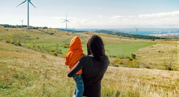 Mother holding her son in nature. Wind turbines in the background.