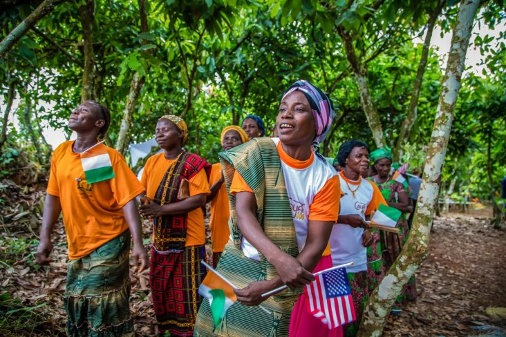 Women singing in a cocoa farm holding the American and Ivoirian flags.