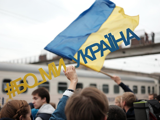 """A person holds a sign """"#Because we are Ukraine"""""""