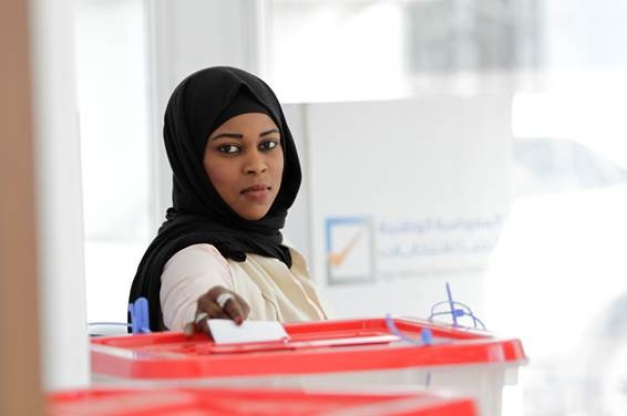 A Libyan woman submits her ballot at an election.