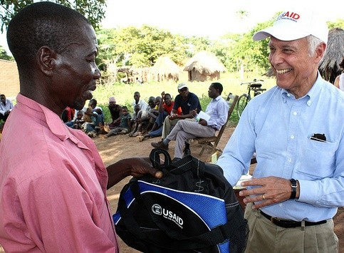 USAID/Zambia Mission Director Dr. Michael Yates offers a customary token of appreciation to a village headman in Zambia's Easter