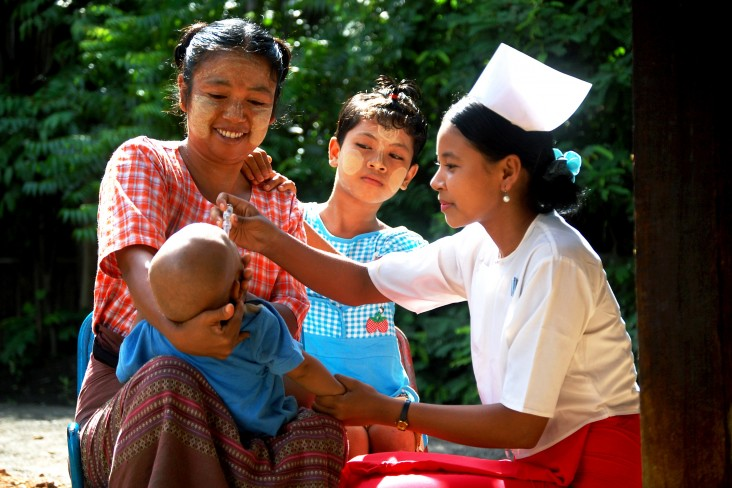A health care provider gives an infant the polio drop in Burma