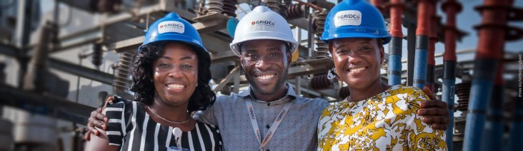 Three GridCo technicians pose in front of an electric power station