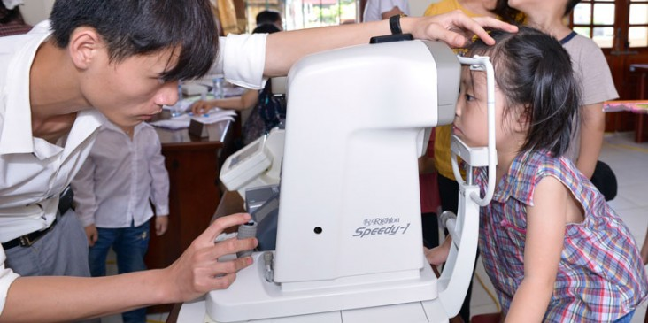 An optometrist examines the site of a young girl.