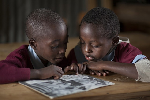 Two Kenyan boys read together while sharing a book.