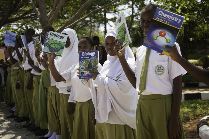 Girls hold up textbooks donated by USAID at a school in Dar es Salaam.