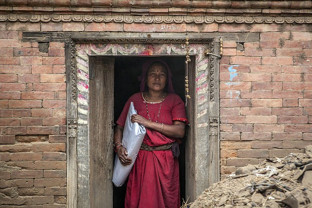 With her house too damaged to live in, she moves to her family's temporary shelter in the courtyard with plastic sheeting.