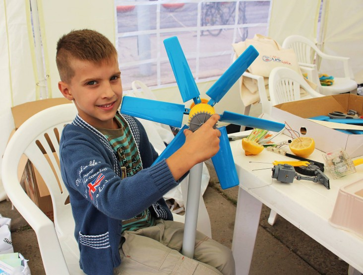 A young enthusiast displays a model of wind turbine he assembled at an Energy Efficiency Lab during a USAID City Day in Sumy.