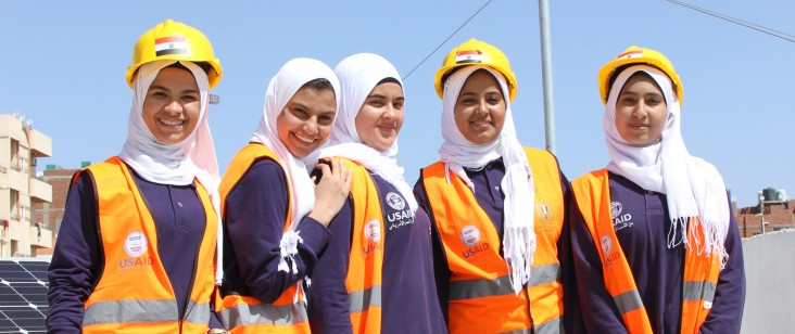 Female students at a vocational student in Hurghada, Egypt stand in front of solar panels.