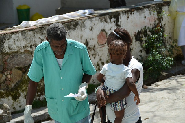 Doctor with mom and baby at St. Justinien Hospital in Cap Haitien, Haiti, where USAID is constructing a new maternity ward.