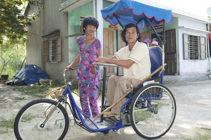 A person with disabilities in Quang Nam Province on a tricycle wheelchair provided with USAID support.