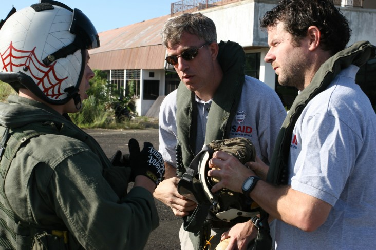 USAID DART team members explain relief supply requirements to a U.S. Navy pilot