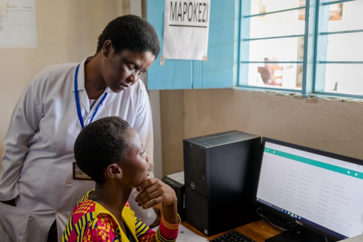 Staff at Ilemela Dispensary in Mwanza region of Tanzania speak with Aflozia's mother to check her in as a new patient. The receptionist illustrates how their new computer system has made patient tracking easier and more reliable.