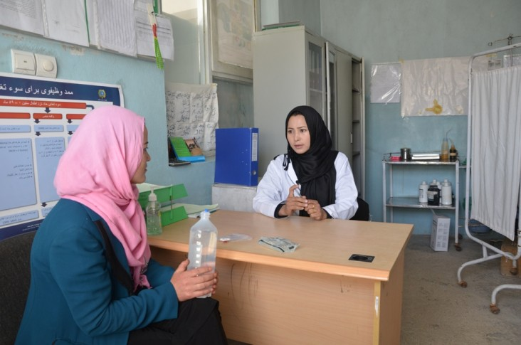A health worker sits with a patient to assess what's the best course of action.
