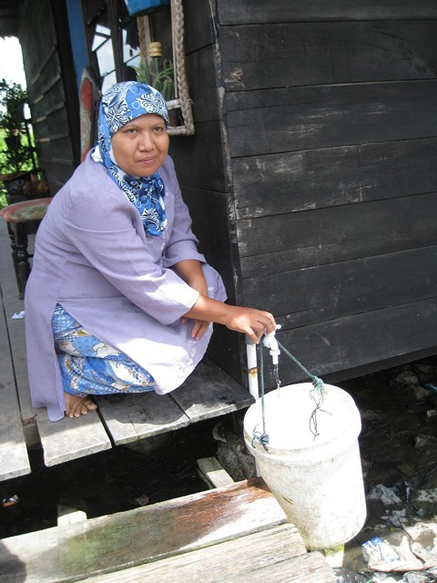 A woman fetching water from her own water tap in Medan, Indonesia.