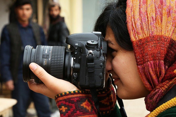 A young photojournalist is looking for the perfect shot, on assignment to capture content for a local company in Kabul.