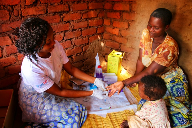 A Community Engagement Facilitator with One Community provides home-based HIV testing service to a woman in rural Machinga, Malawi.