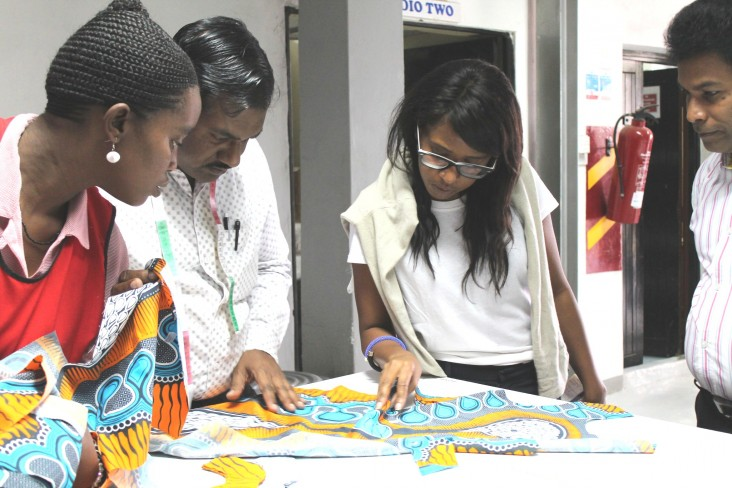 Designer Doreen Mashika, center, examines dresses for the Anthropologie collection with her team at the Nairobi factory.