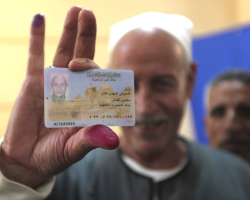 Egyptian Rezq Anan shows his ID card and ink-stained finger after casting his vote at a polling station in Mansura, March 19, 20