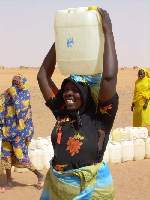 A woman carries water in Abu Shook camp for internally displaced persons near El Fasher.