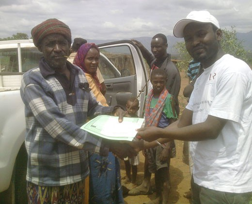 An Ethiopian pastoralist receives a copy of his new insurance policy.