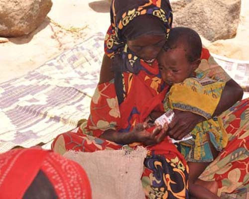 An Ethiopian woman feeds Plumpy'nut peanut paste to her 1-year-old daughter at a therapeutic feeding center.