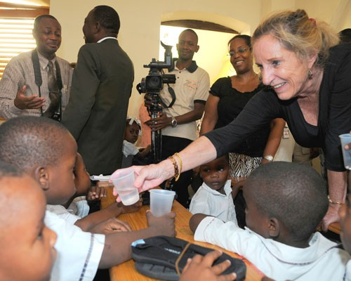 U.S. Ambassador Pamela White hands a child a cup of water while distributing medicine to control the spread of lymphatic filaria