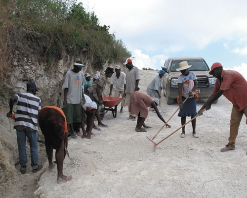 Members of the Fond Baptiste community carry out labor-intensive road maintenance.