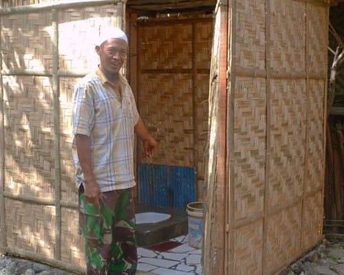 Syamsudin Sitaba of Empoang Utara in Jeneponto district shows his newly installed toilet following an IUWASH–assisted Ministry o