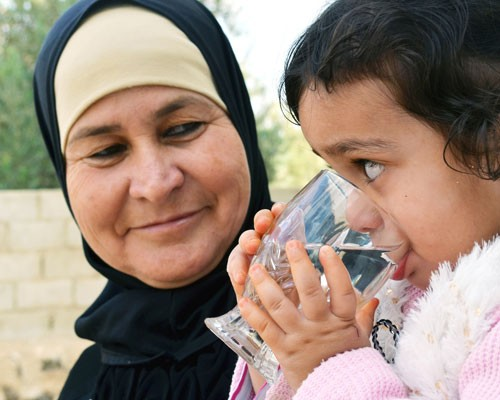 Al Khaldi's 2-year-old granddaughter drinks from a glass as her grandmother looks on.