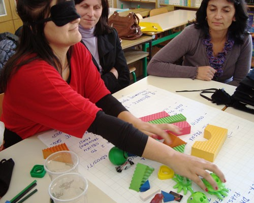 Blindfolded teachers participate in a training exercise.