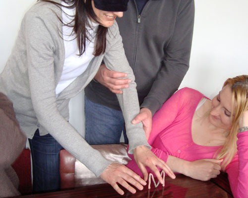 Blindfolded teachers arrange shapes as part of a training exercise.