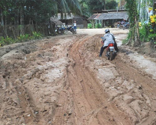 Residents of Olutanga Island like Lolita Singahan travel over unpaved roads spewing dust in summer and turning muddy during the