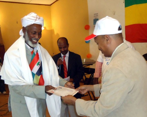 Sultan Mohammed Hassen Gababa, traditional leader of the Gari clan, receives a certificate from Shiferaw Tekle-Mariam, minister