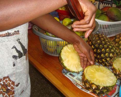 A mother participating in a nutrition education program at Rwanda's Kibagabaga Hospital cuts pineapple during a fruit salad demo