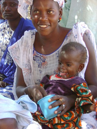 A Sengalese mother feeds her baby daughter fortified cereal for better nutrition.