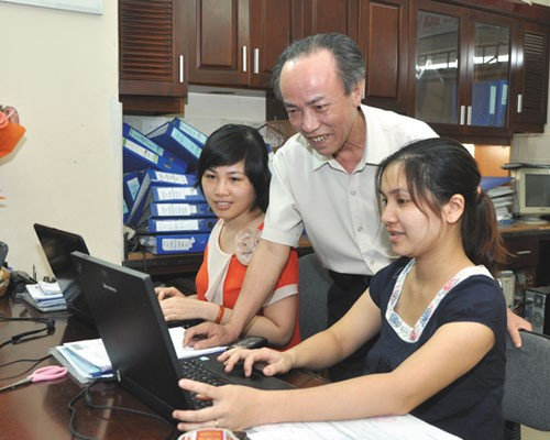 Vu Xuan Tien consults with his accounting and auditing staffers in his office in Hanoi.