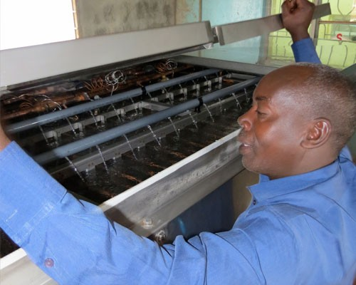 Joseph Githahu checks the cooling system for the milk he collects.