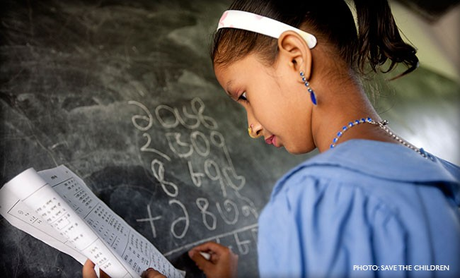 Image of young girl writing on chalkboard in Bangladesh