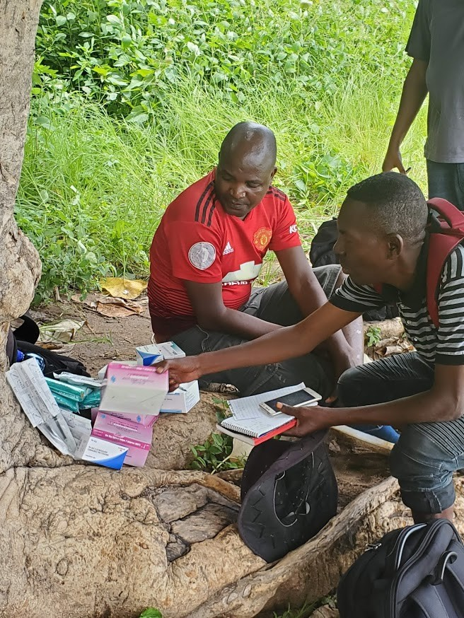 Baxton Kamanga (right) reviewing the contents of the drone. / Ryan Triche, GHSC-PSM