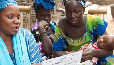 A health workers shares information with two women, one of whom is holding a baby.