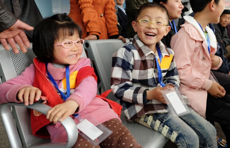 Two children with glasses sit in seats in China