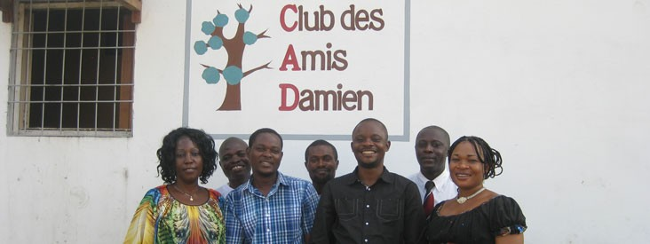 Staff members stand in front of a sign for Club Des Amis Dmaien