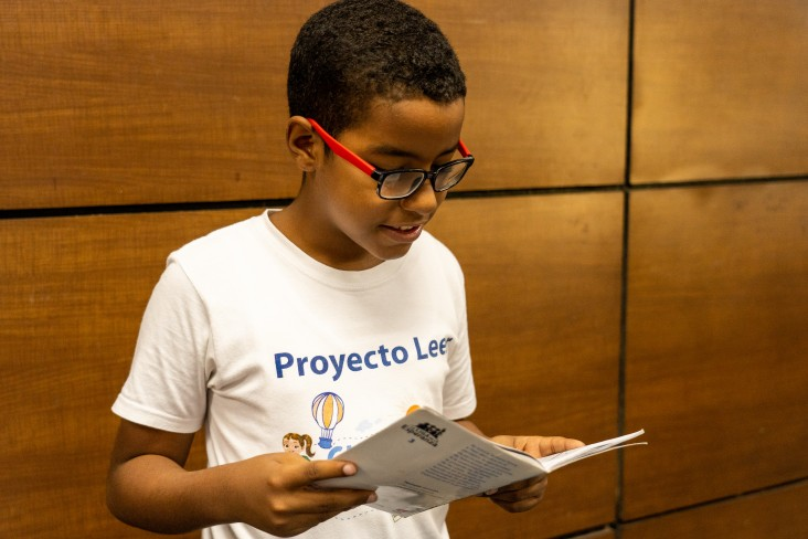 Child reads and focuses on USAID READ Project's book.