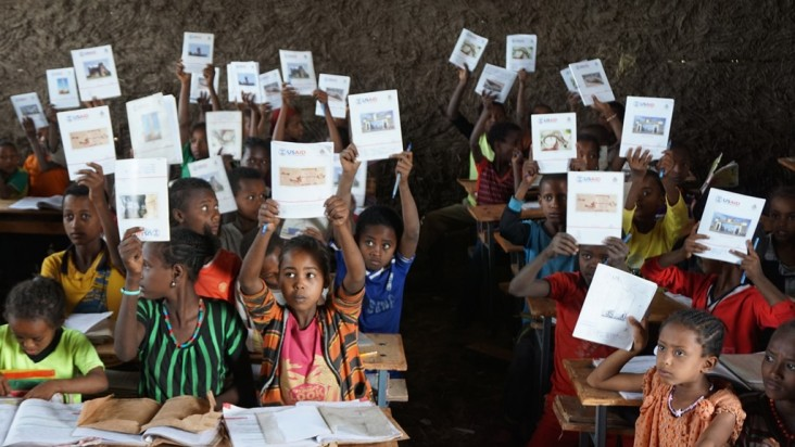 Students in a classroom with workbooks purchased by USAID. In total, USAID purchased more than 8.2 million workbooks for distrib