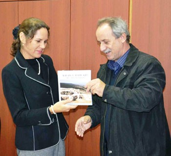 Mayor Burim Berisha shows USAID Representative Tanya Urqieta a tourism promotional book that resulted from Municipality-funded e