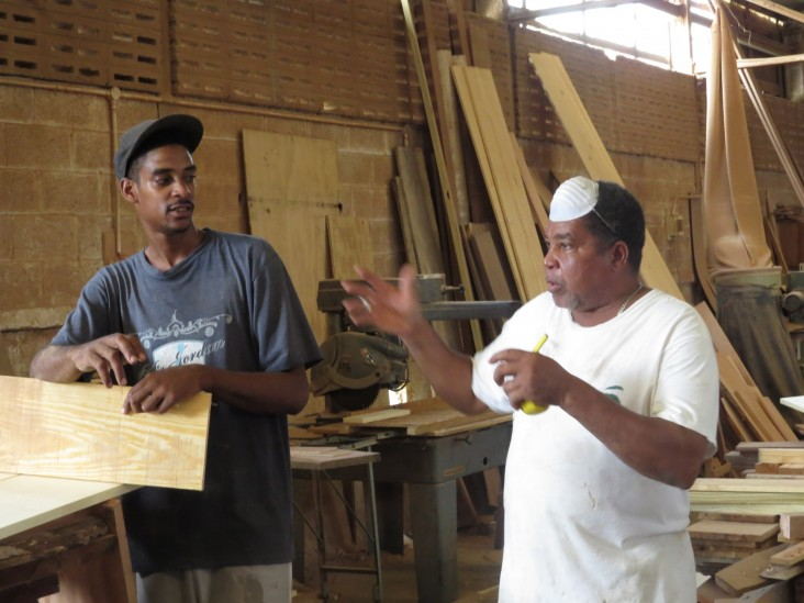 Craftsman Julius Charles passes on his knowledge to the young apprentices.