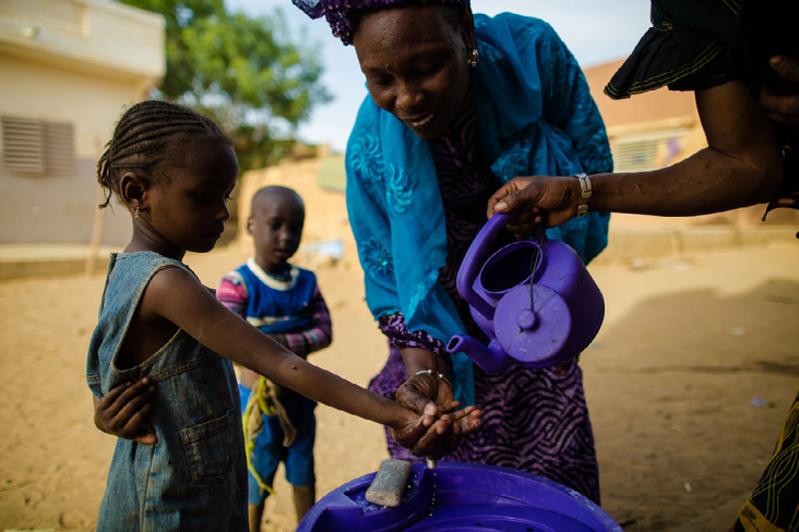 Hapsatou Ka is a USAID-trained, community-based solution provider in Senegal. She teaches local children the importance of sanitation by washing their hands prior to eating lunch.