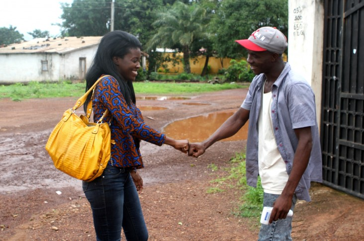 Mariama Keita and Alseny Touré greet each other at the French Red Cross site near the Ebola Treatment Unit in Forécariah, Guinea