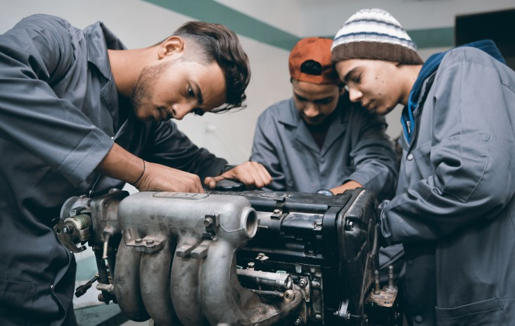 Three young men work on a car engine.